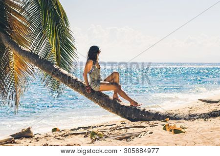 poster of Traveler girl relaxing on tropical beach. Young girl traveler relaxing in vacation. Traveler relaxing on tropical beach in vacation. Girl in vacation relaxes on beach in summer day. Traveler. Summer. Vacations. Woman relaxing on the beach. .Vacation lifes