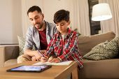 education, family and homework concept - happy father and son with tablet computer writing to notebo poster