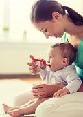 family, food, child, eating and parenthood concept - happy smiling mother with puree and spoon feedi poster