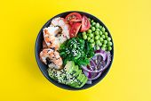 Poke Bowl With Red Shrimps And Vegetables In The Dark Bowl In The Center Of The Yellow Background.to poster