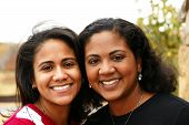 picture of mother daughter  - Two young minority sisters outside hugging outside - JPG