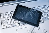 A Silver Laptop With A Broken Keyboard, Tablet With A Cracked Display And Black Phone. A Close-up Pi poster