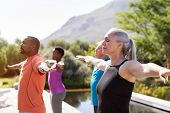 Group of senior people with closed eyes stretching arms outdoor. Mature yoga class doing breathing e poster