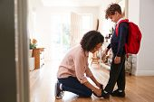 Single Mother At Home Getting Son Wearing Uniform Ready For First Day Of School poster
