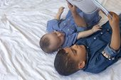 Two Little Brothers Reading A Book. Infant Kids Lying On The Bed And Read The Tale Before Sleeping.  poster