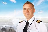 Airline pilot wearing uniform with epaulettes with passenger aircraft in background