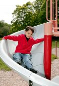 stock photo of children playing  - young male child playing on the slide at a playground - JPG