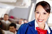 picture of air hostess  - Beautiful air stewardess in an airplane cabin smiling - JPG