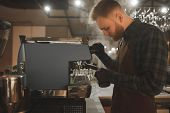 Barista Steaming Milk In Pinscher. Portrait Of Bearded Concentrated Barista Preparing Cappuccino In  poster