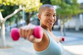 Portrait of happy bald woman exercising while looking at camera. Smiling girl doing sports outdoors  poster