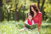 Happy mother and daughter read a book in summer park. Beauty nature scene with family outdoor lifest poster