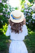 Girl In A Straw Hat With A Blue Ribbon On A Spring Afternoon. Back View. Trendy Casual Summer Or Spr poster