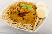 foto of ayam  - Dry Curry Mee - Malaysian chicken curry with coconut milk and noodles served with boiled egg on a woven mat.