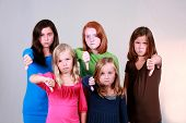 picture of school child  - diverse group of pretty preteen girls giving thumbs down sign - JPG