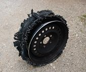 stock photo of blown-up  - Damaged tire after tire explosion at high speed on highway - JPG
