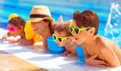 stock photo of sisters  - Happy family in the pool - JPG
