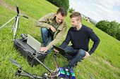 stock photo of drone  - Young male engineers discussing over digital tablet and laptop by UAV drone in park - JPG