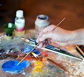 stock photo of pigment  - Hand of the artist with a paintbrush and Artistic equipment - JPG
