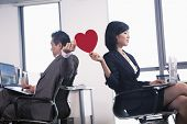 stock photo of office romance  - Work romance between two business people holding a heart - JPG