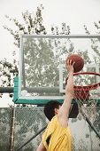 stock photo of slam  - Slam dunk by young man - JPG