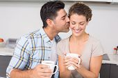 Happy woman drinking coffee getting a kiss from partner at home in kitchen