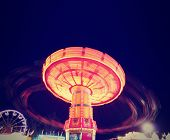 foto of carnival ride  - a fair ride shot with a long exposure at night done with a retro vintage instagram filter - JPG