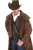 pic of wrangler  - A cowboy in a vest and leather duster and hat looking down - JPG