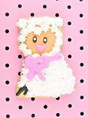 stock photo of poka dot  - Spring themed cookie decorated as a sheep on a pink paper background - JPG