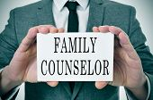 stock photo of nameplates  - a man wearing a suit sitting in a desk with a desktop nameplate in front of him with the word family counselor - JPG