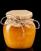 picture of jar jelly  - Orange jelly in glass jar isolated on black background - JPG