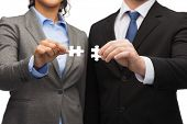 business concept - businessman and businesswoman trying to connect puzzle pieces in office