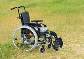 picture of lame  - Empty used wheelchair standing on the green grass - JPG