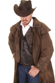 stock photo of wrangler  - A cowboy in a vest and leather duster and hat looking down - JPG
