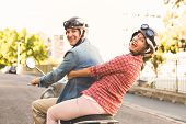 stock photo of scooter  - Happy mature couple riding a scooter in the city on a sunny day - JPG