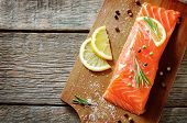 stock photo of salmon steak  - salmon with lemon and rosemary on a dark wood background - JPG