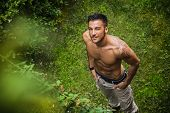 picture of grassland  - Good looking shirtless fit male model looking up with wink outdoors on grassland - JPG