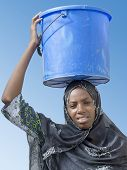 image of afro  - Afro beauty carrying a bucket of water on her head - JPG