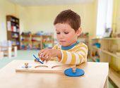 picture of montessori school  - Boy engaged in the Montessori classroom - JPG