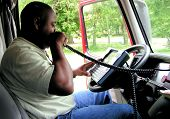 image of 18 wheeler  - An African American male using an on board computer  - JPG