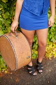 foto of mini-skirt  - Detail of antique hat case being held by girl wearing blue mini skirt - JPG