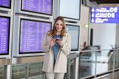 picture of terminator  - Young woman at international airport checking electronic board holding passport and ticket and waiting for her flight - JPG