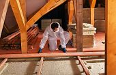 stock photo of insulator  - Man laying thermal insulation under the roof  - JPG