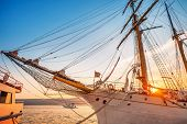stock photo of tall ship  - Old sailing ship in the rays of light of the setting sun in the port - JPG