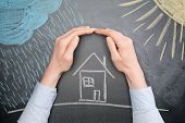 stock photo of insurance-policy  - A young businesswoman protects a house from the elements  - JPG