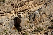 image of hamlet  - Traditional stone houses in a small cliff hamlet near Sroot in the Jebel Akhdar mountains of the Sultanate of Oman - JPG