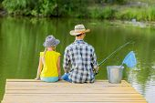 image of father daughter  - Rear view of father and daughter sitting on bridge and fishing - JPG