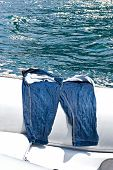 picture of wet pants  - Wet jeans on the boat drying under the sun at seacoast - JPG