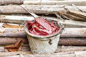 pic of grease  - Close up dirty grease and wooden paddle in old bucket on heap of lumber - JPG