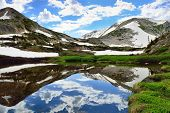 picture of snowy hill  - Snowy Range Mountains and alpine lake with reflection in Medicine Bow Wyoming in summer - JPG