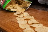 stock photo of potato chips  - Potato Chips Coming Out Of A Bag Onto A Wood Board - JPG